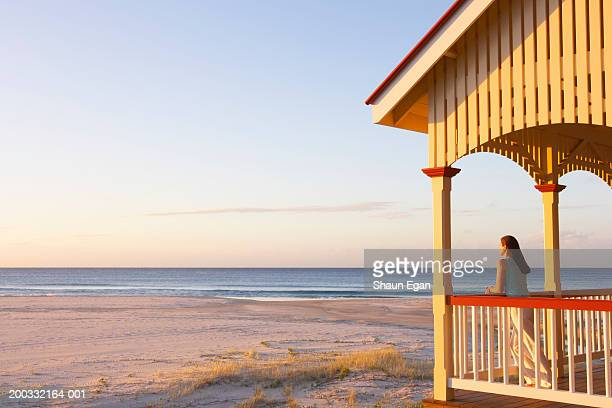 Woman leaning on balcony by beach, sunset