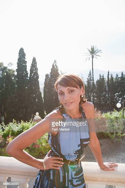 woman leaning on balcony railing - beautiful dominant women stock pictures, royalty-free photos & images