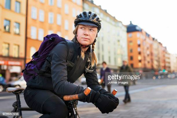 woman leaning on bicycle in street - bicycle messenger stock pictures, royalty-free photos & images