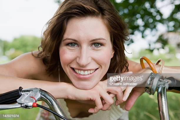 Woman leaning on bicycle outdoors