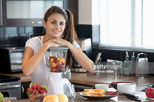 Woman leaning on blender full of fruit
