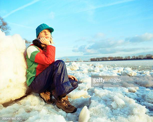 woman leaning on block of ice, looking at frozen river - frozen 2 stock pictures, royalty-free photos & images