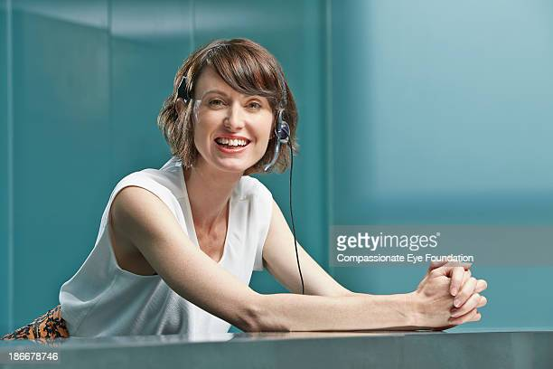 woman leaning on cabinet with phone headset - une seule femme d'âge moyen photos et images de collection