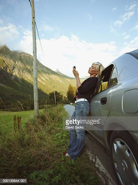 woman leaning on car, dialing on mobile phone, side view - generic location stock pictures, royalty-free photos & images