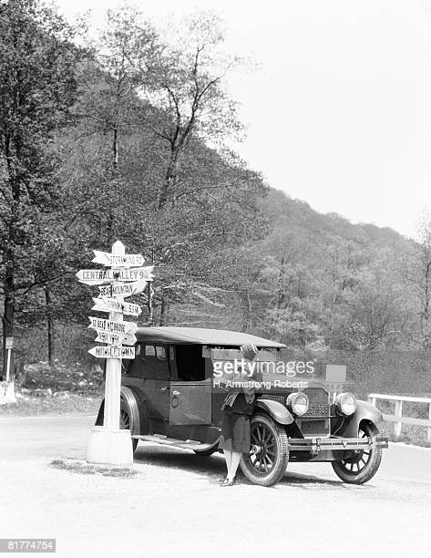woman leaning on car looking at road map and signs with arrows pointing to selected towns indicating mileage. - 1920 car stock photos and pictures