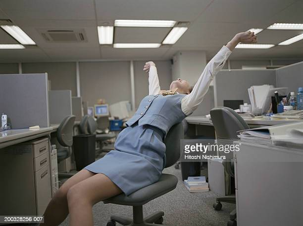 Woman leaning on chair, stretching arms in office