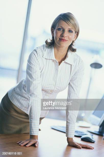 Woman leaning on desk in office, portrait