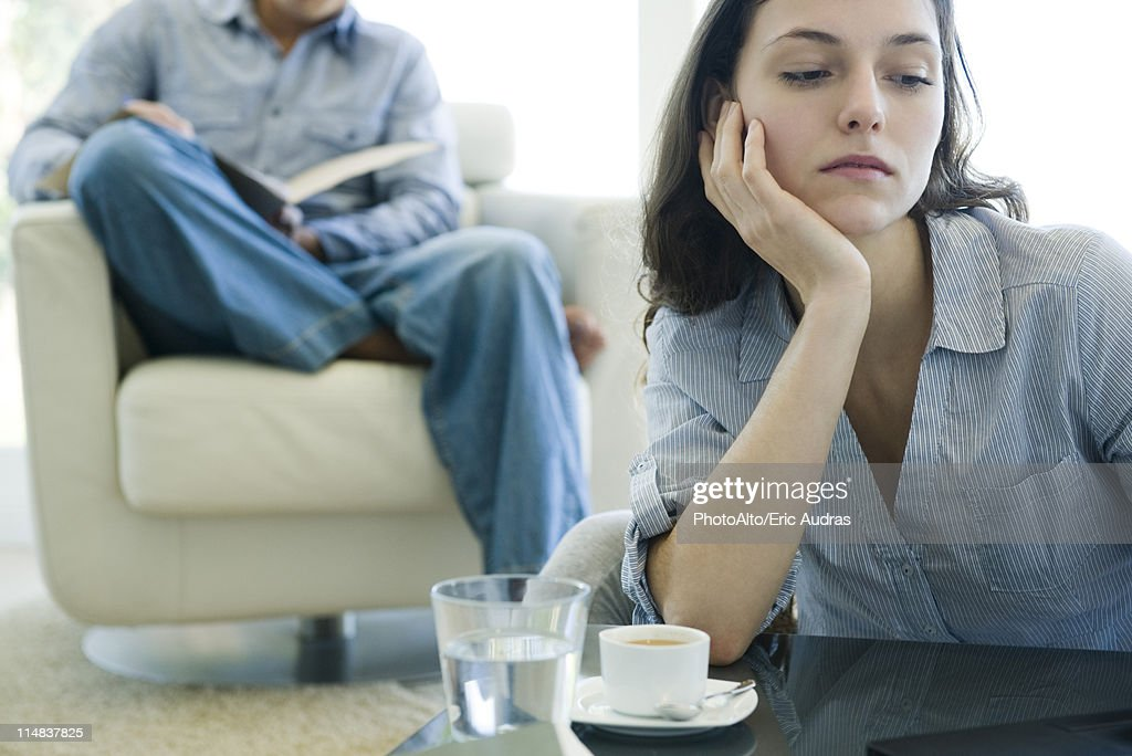 Woman leaning on elbow looking sad, man reading on sofa in background : Stock Photo