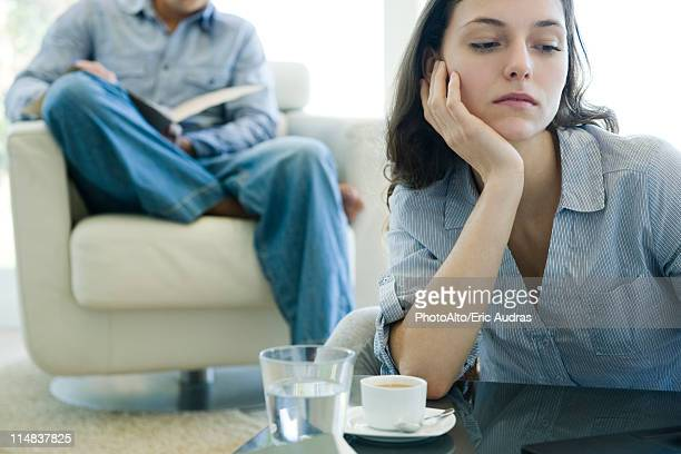 woman leaning on elbow looking sad, man reading on sofa in background - relationship difficulties stock pictures, royalty-free photos & images
