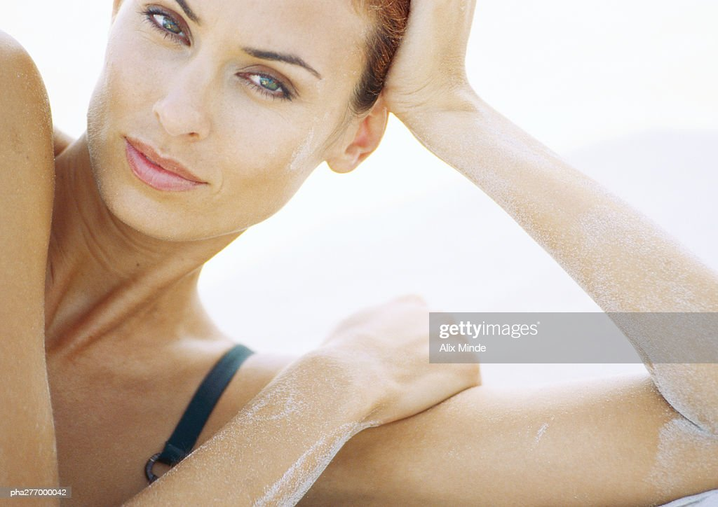 Woman leaning on elbow with sand on arms, looking at camera : Stockfoto