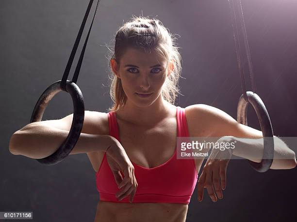 woman leaning on gymnast rings