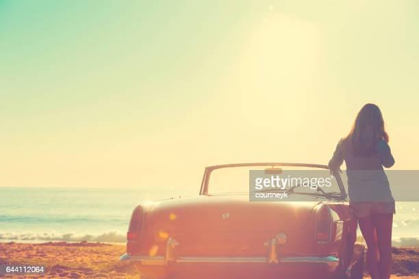 Mujer, apoyado en su coche en la playa. El coche es un convertible clásico. Ella es looing hacia fuera en el océano en el amanecer o atardecer. Mirando muy relajado de vacaciones.