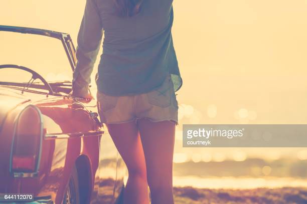 woman leaning on her car at the beach. - beautiful bums stock pictures, royalty-free photos & images