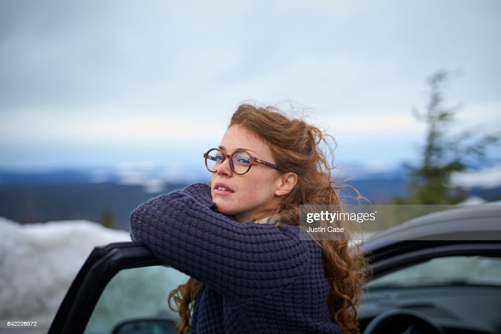 woman leaning on her car door overlooking landscape while having a break from driving : Stock-Foto