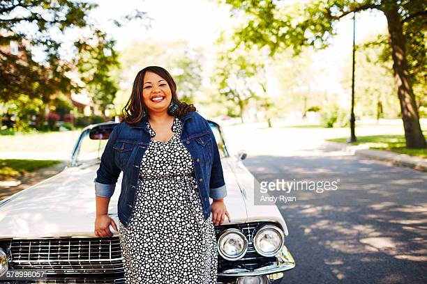 woman leaning on hood of vintage convertible. - heavy stock pictures, royalty-free photos & images