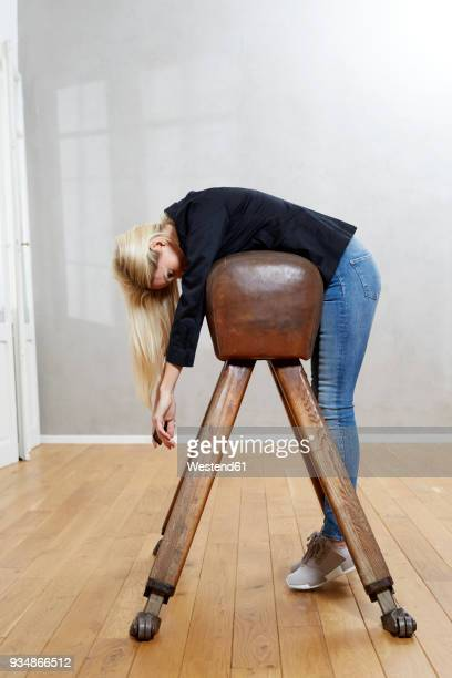 Woman leaning on pommel horse