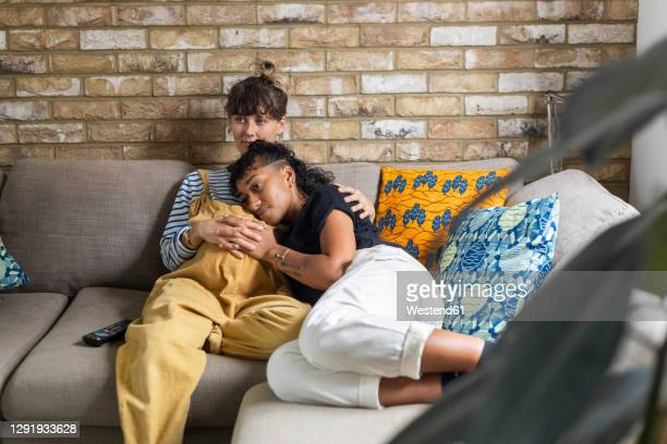 woman leaning on pregnant girlfriend stomach while sitting at home - pregnant stock pictures, royalty-free photos & images