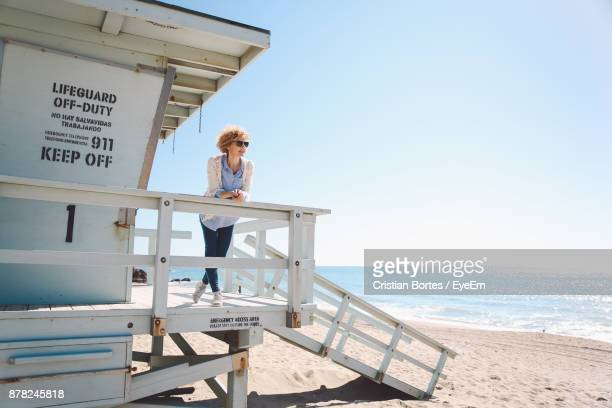 Woman Leaning On Railing Of Lifeguard Hut At Beach Against Clear Sky