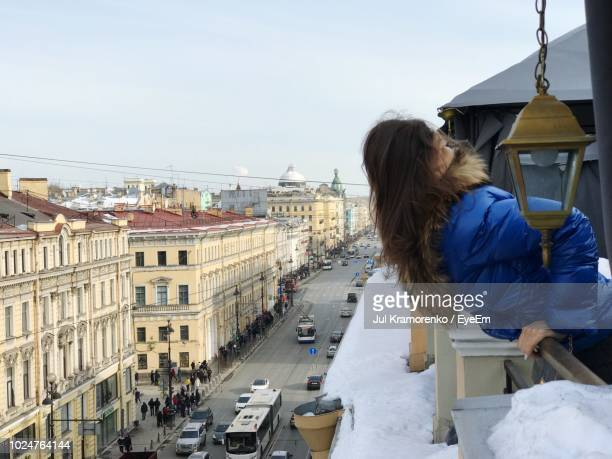 Woman Leaning On Railing While Looking At City