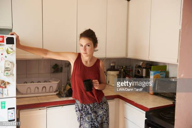 Woman leaning on refrigerator drinking coffee