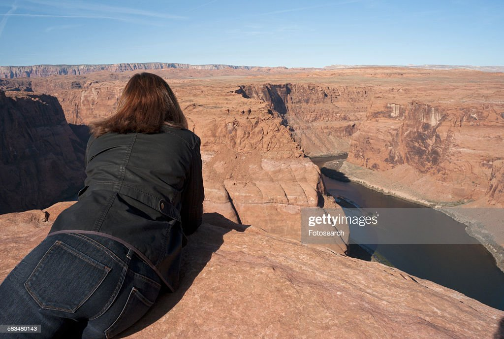 Woman leaning on rock looking at a view : Stock Photo