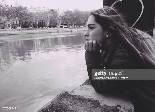 Woman Leaning On Stone Wall Over Water