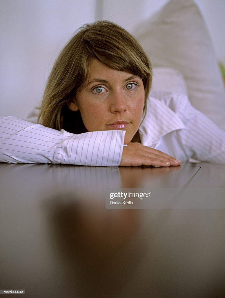 Woman leaning on table, close up : Stock Photo