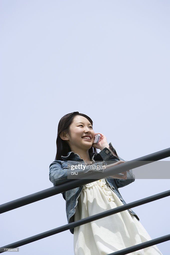 Woman leaning on the railing and using mobile phone under the blue sky, low angle view, blue background, copy space, Japan : Stock Photo