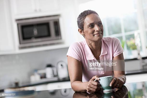 A woman leaning on the smooth countertop of her kitchen unit, with a cup of coffee.