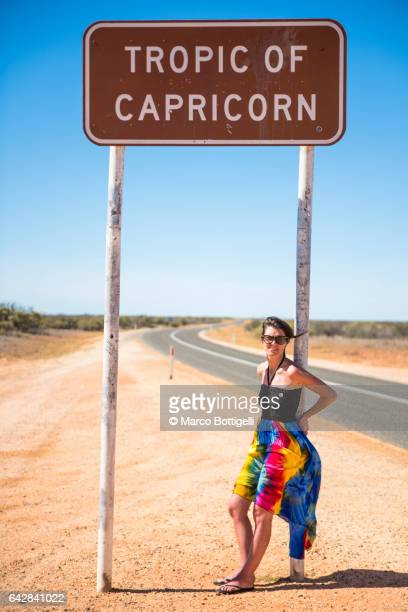 Woman leaning on the Tropic of Capricorn road sign. Western Australia.