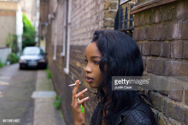 Woman leaning on the wall smoking a cigarette