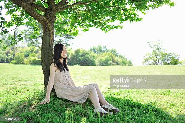 Woman leaning on tree in nature.