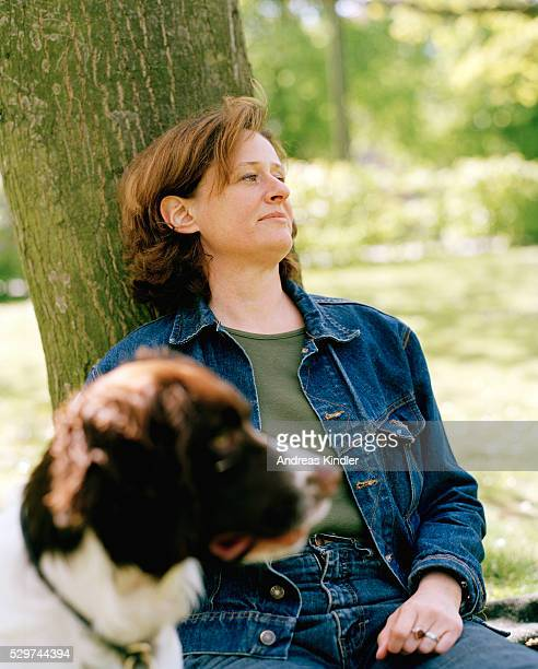 Woman leaning on tree with dog sitting in front