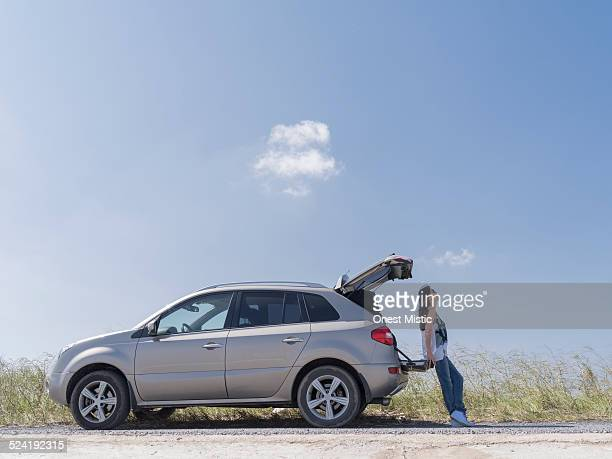 Woman leaning on trunk of car