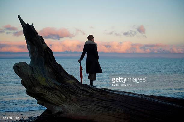 Woman leaning on umbrella standing on large driftwood tree trunk on beach