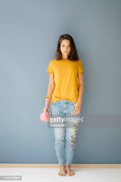 woman leaning on wall, holding flamingo shaped watering can - ganzkörperansicht stock-fotos und bilder