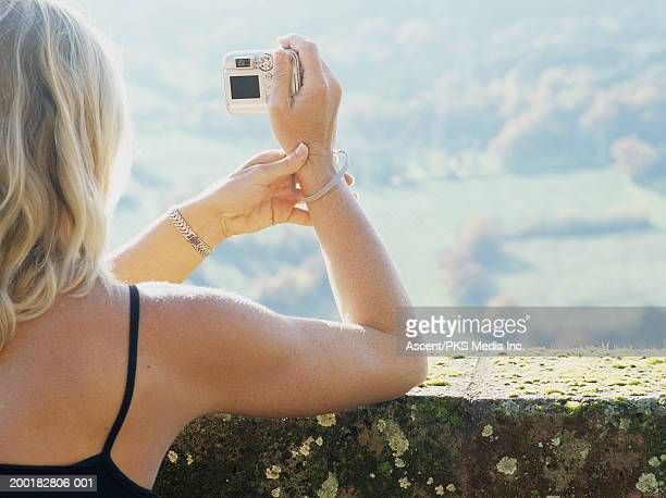 Woman leaning on wall, taking photograph with digital camera