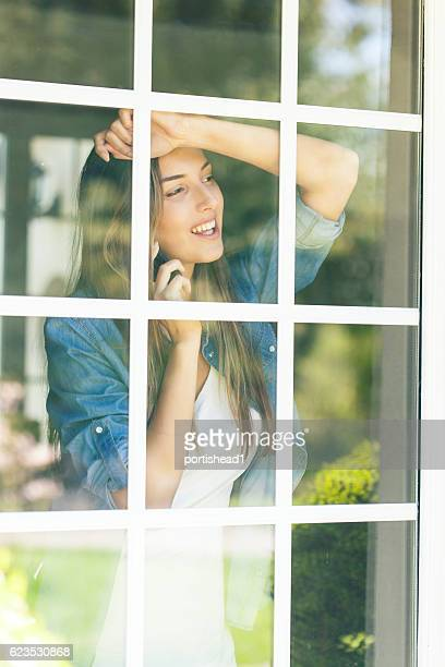 Woman leaning on window and talking on phone
