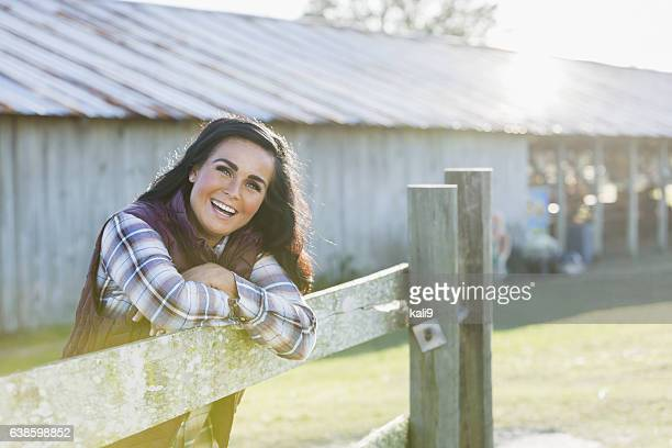 Woman leaning on wooden fence outside farm building