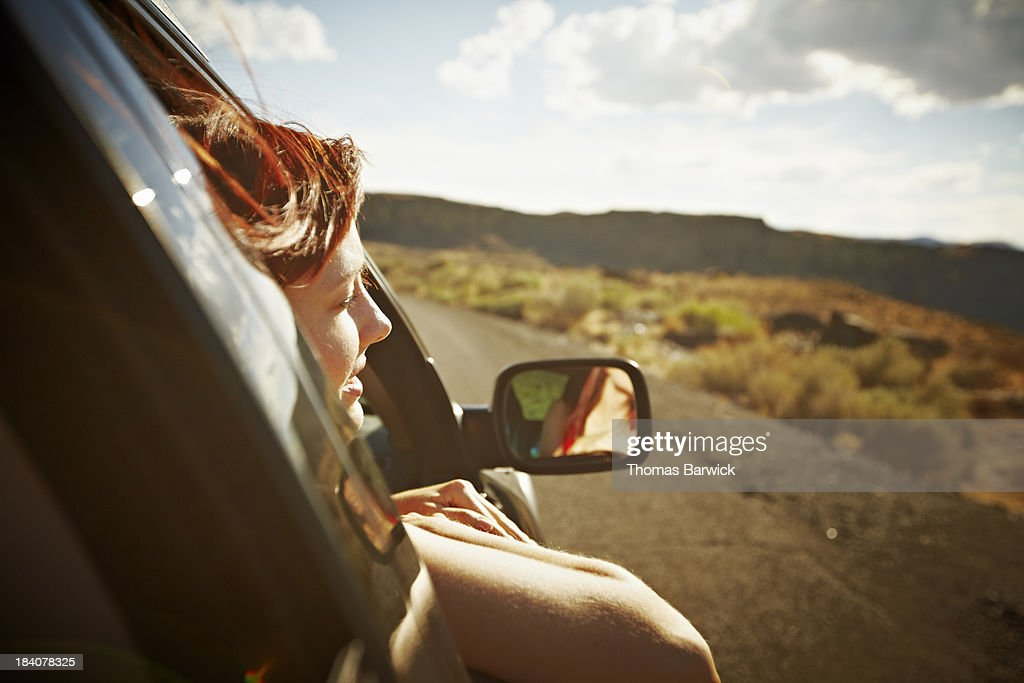 Woman leaning out front window of car : Stock Photo
