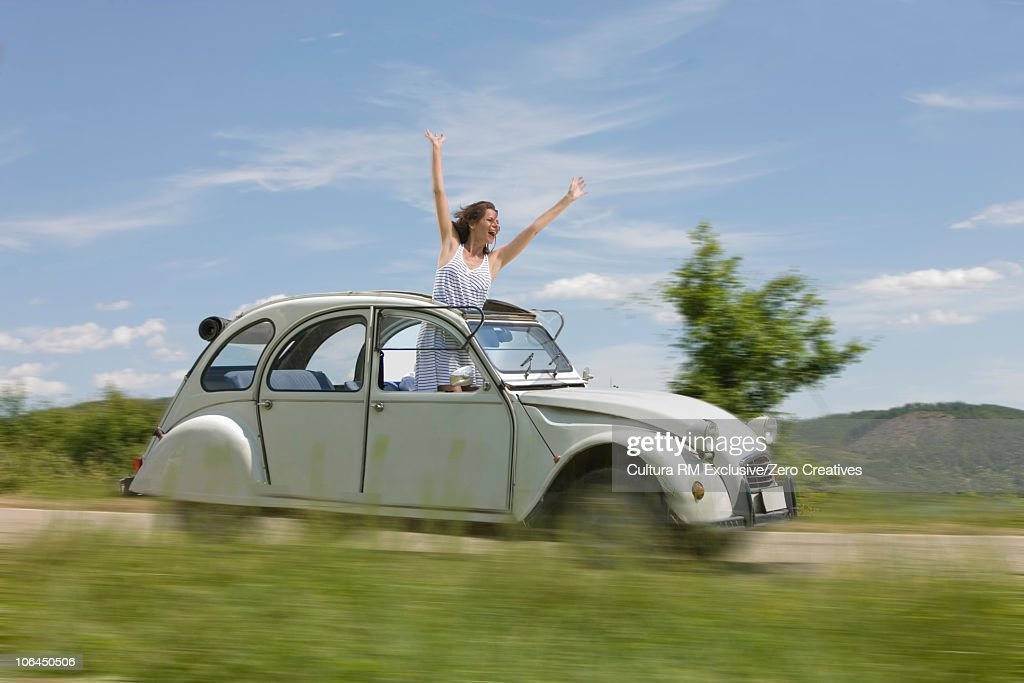 Woman leaning out of a driving car : Stock Photo