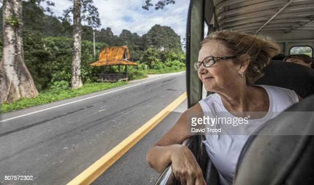 Woman leaning out of bus window in Thailand