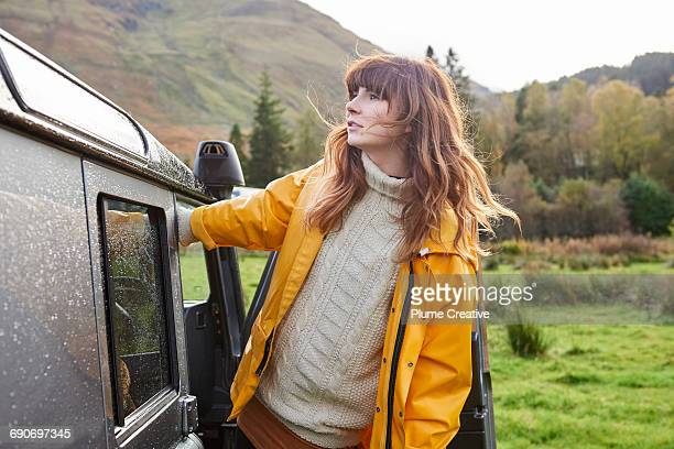 Woman leaning out of car looking at landscape