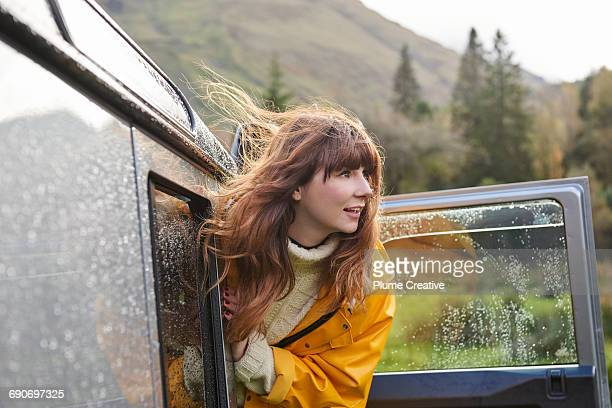 Woman leaning out of car looking into landscape