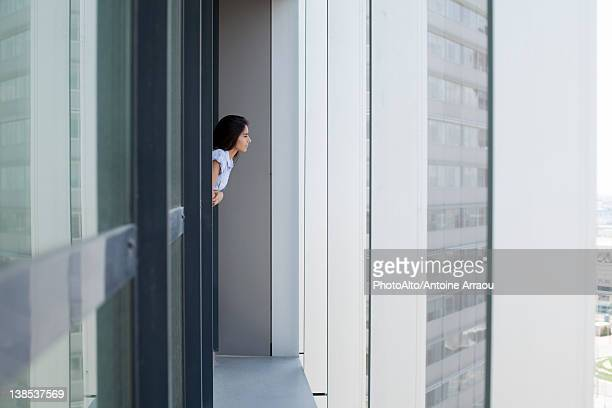 Woman leaning out of window looking at view