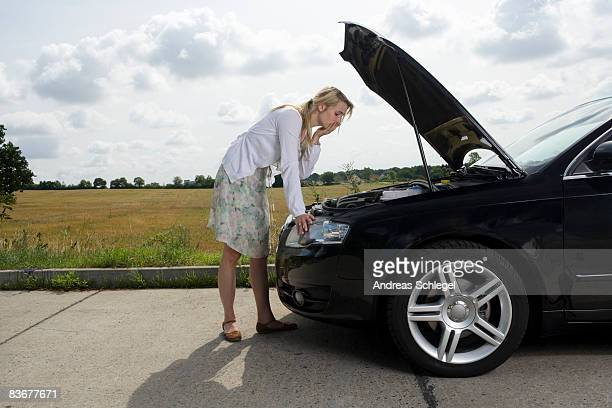 A woman leaning over an open bonnet at the roadside