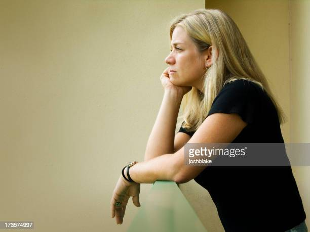 Woman leaning over ledge resting head in hand in thought