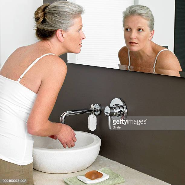 Woman leaning over sink and looking in mirror