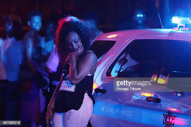 A woman leans against a police squad car as she grieves at the scene where five people were shot including a 22yearold man who was killed in the...