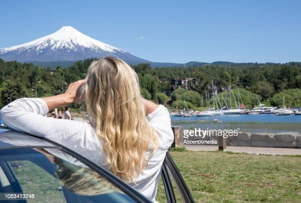 mujer se inclina contra el coche y mira volcán nevados - pucon fotografías e imágenes de stock